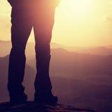 Ноги hiker женщины в туристских ботинках стоят на пике горы скалистом день солнечный стоковые изображения rf