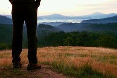 Ноги hiker женщины в туристских ботинках стоят на пике холма, сухой траве в луге стоковые изображения rf