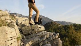 Ноги hiker женщины стоят на краю скалы горы против красивого пика гор видеоматериал
