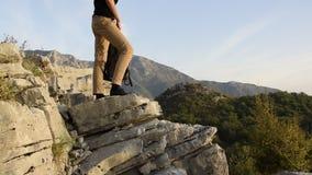 Ноги hiker женщины стоят на краю скалы горы против красивого пика гор сток-видео