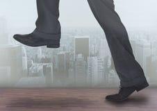 Ноги ` s бизнесмена над городом стоковая фотография
