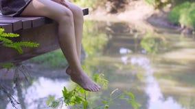 Ноги ` s женщины вися над краем деревянной молы видеоматериал
