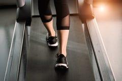 Ноги ` s женщины мышечные на третбане Стоковые Изображения RF