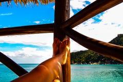 Ноги ` s женщины на балконе смотрят на море на тропическом острове стоковое фото rf