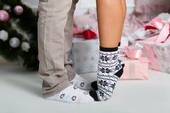 Ноги ` s людей в носках с пингвинами и женские ноги стоят на пальцах ноги в носках с картинами снежинок Стоковое фото RF