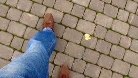 Ноги ` s людей идя вдоль мостоваой с плитками тротуара в городе акции видеоматериалы