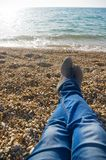 Ноги ` s людей на предпосылке моря приставают к берегу стоковое фото