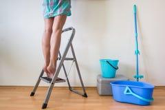 Ноги ` s молодой женщины на лестнице и руке с щеткой Стоковые Изображения