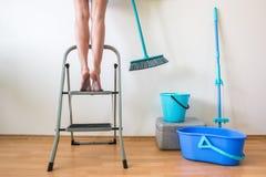 Ноги ` s молодой женщины на лестнице и руке с щеткой Стоковые Фото