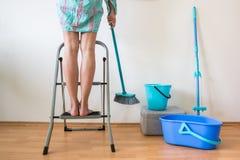 Ноги ` s молодой женщины на лестнице и руке с щеткой Стоковое Изображение