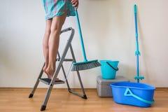 Ноги ` s молодой женщины на лестнице и руке с щеткой Стоковое фото RF