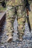 Ноги ` s солдата с оружиями на дороге Стоковые Фото
