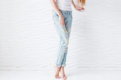 Ноги Women's в голубых джинсах с белым pedicure на белой предпосылке Стоковые Фотографии RF