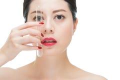 Ноготь губ азиатской девушки красный, держа трубку химической лаборатории Стоковая Фотография