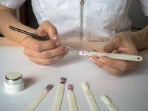 ноготь конструкции искусства Женский мастер рисует на подсказках стоковая фотография