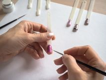ноготь конструкции искусства Женский мастер рисует на подсказках стоковое фото rf
