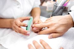Ноготь маникюра формируя с зеленой пилочкой для ногтей стоковое изображение