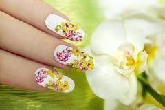 Ноготь с картиной покрашенных орхидей. Стоковые Фото