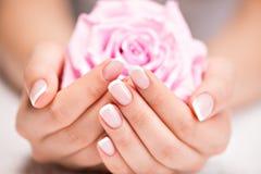 Ногти красивой женщины с французским маникюром и подняли стоковые фотографии rf