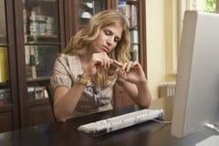 Ногти опиловки женщины над компьютером в комнате исследования Стоковые Изображения