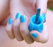 Ногти с голубое поднимающим вверх заволакивания и щетки laque близкое стоковое фото