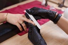 Ногти Manicurist храня для того чтобы получить идеальную форму стоковые изображения