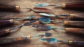 Ножи палитры художника на деревянной деревенской таблице, ретро стилизованном стоковое изображение rf