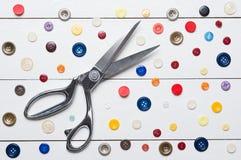 Ножницы и кнопки для handmade шить на белом деревянном столе Стоковая Фотография