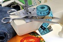 Ножницы и метр белошвейки на швейной машине стоковое фото