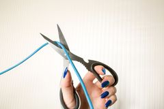 Ножницы отрезали провод соединения на бежевой предпосылке Стоковые Фото