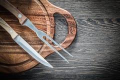 Нож вилки мяса высекая доску на деревянной предпосылке Стоковое Изображение