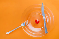 Нож, вилка, прозрачная плита и малый томат вишни на ем Стоковое Фото
