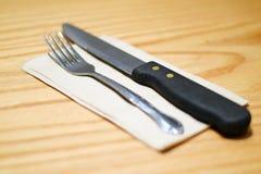 Нож вилки и стейка на коричневой салфетке Стоковые Фото