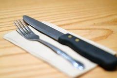 Нож вилки и стейка на коричневой салфетке Стоковые Изображения