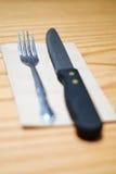 Нож вилки и стейка на коричневой салфетке Стоковая Фотография