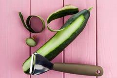 Нож для очищая овощей и плодов с огурцом с, который слезли кожей на розовой предпосылке стоковые фотографии rf