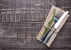 Нож и вилка внутри полотенца кухни на деревянной доске Стоковые Изображения