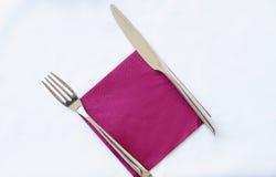 Нож и вилка на фиолетовой салфетке на белой предпосылке Стоковые Фото