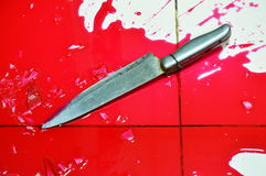 Нож и серия крови брызгают на плиточном поле Стоковые Фото