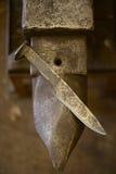 Нож кованой стали руки на наковальне Стоковая Фотография RF