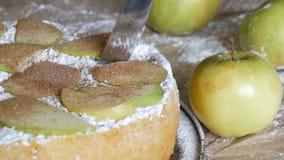 Нож режет часть очень вкусного свежо испеченного сочного яблочного пирога charlotte на предпосылке зеленых яблок традиционно акции видеоматериалы