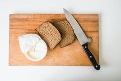 Нож с хлебом с маслом на прерывая доске Стоковая Фотография RF