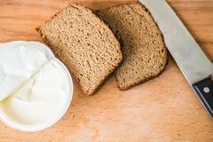 Нож с хлебом с маслом на прерывая доске Стоковые Изображения