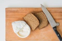 Нож с хлебом с маслом на прерывая доске Стоковое Изображение RF
