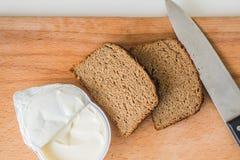 Нож с хлебом с маслом на прерывая доске Стоковые Изображения RF