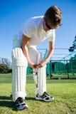 Ноколенник игрока сверчка нося пока стоящ на травянистом поле стоковое изображение