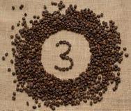Номера от кофейных зерен на предпосылке мешковины стоковая фотография rf