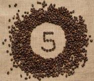 Номера от кофейных зерен на предпосылке мешковины стоковое фото