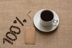 номера 100% от кофейных зерен с чашкой кофе стоковое фото rf