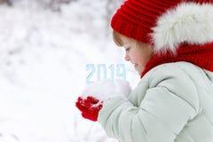 Номера предстоящего года в руках ребенка стоковое изображение